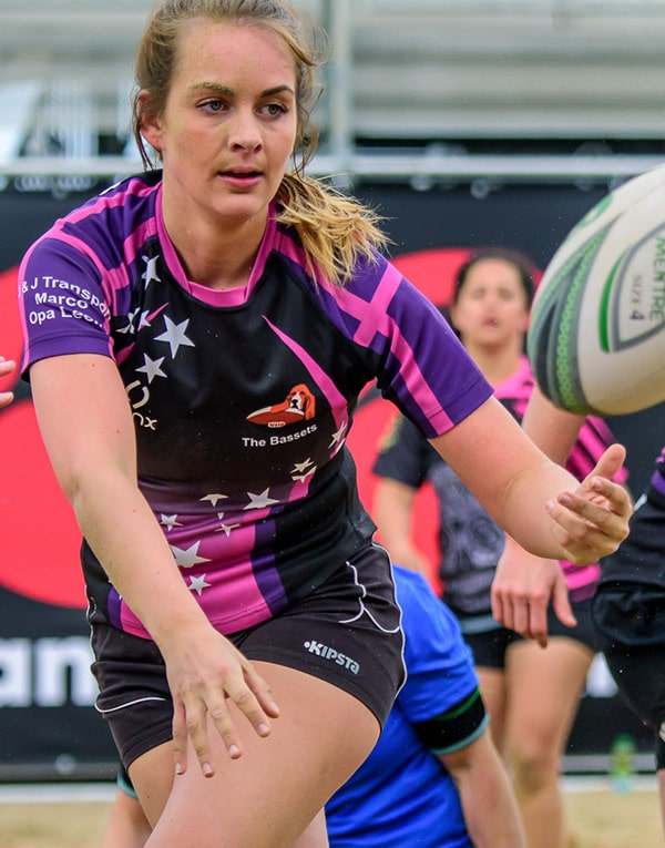 A woman passing a rugby ball